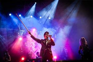 Sänger als Robbie Williams im buntem Bühnelicht auf einem Stadtfest in Kiel
