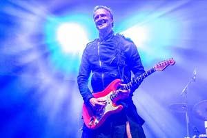 Gitarrist Stephan Vollber mit hellem Scheinwerfer im Hintergrund