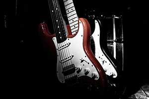 Titelbild für Partymusik. Zwei Gitarren im Gitarrenständer auf der Bühne